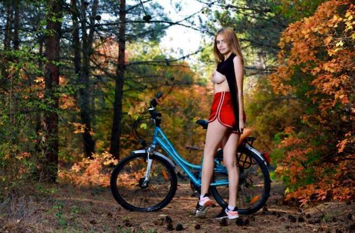 Dakota Pink на велосипеде в осеннем лесу