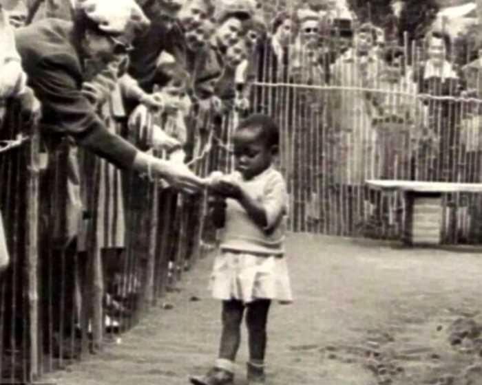 История знаменитого фото: Посетители кормят девочку-африканку в «человеческом зоопарке»